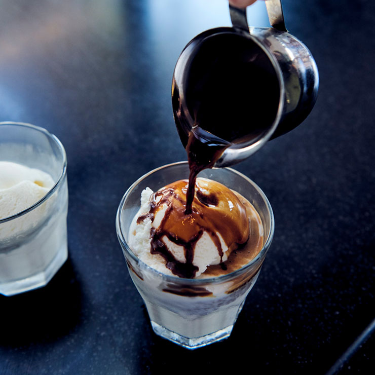 Espresso shot being poured over ice cream in a glass on a counter