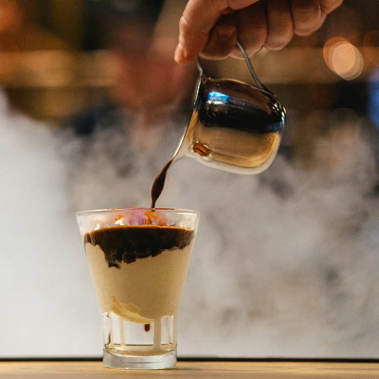 A barista pouring espresso over a small glass of gelato with a cloud of mist in the background
